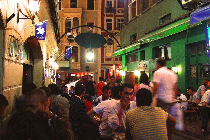 oświetlona, wąska uliczka w Stambule, zatloczona przez siedzących przy barach i restauracjach tubylców