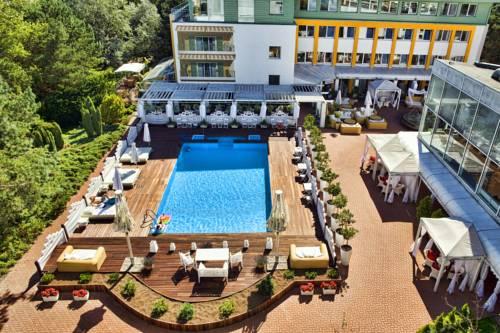 Basen z leżakami oraz widokiem na ogród w Hotel Bryza Resort & SPA, Jurata, Polska