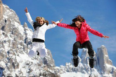 dwie młode kobiety ubrane w zimowe stroje skaczące radośnie na tle ośnieżonych gór we Włoszech