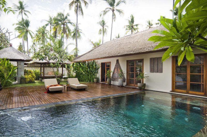 elegancki domek letniskowy z basenem i ogrodem, w tle palmy, Bali