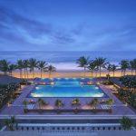 widok z balkonu hotelu na oświetlony ogórd z palmami i basenem, w tle plaża, Bali - Indonezja
