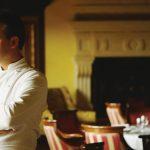 szef kuchni stojący z założonymi rękami we wnętrzu eleganckiej restauracji