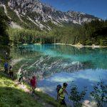 grupa turystów odbywająca pieszą wędrówkę, w tle błękitny staw i góry, Austria