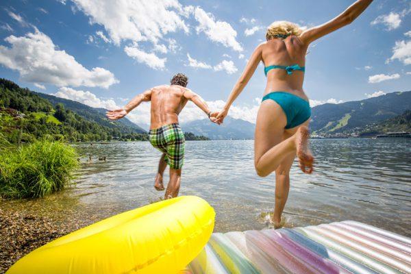 para turystów biegnąca do wody w strojach kąpielowych