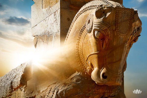 kamienna rzeźba konia w Persepolis na tle wschodzącego słońca