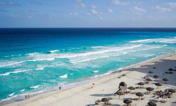 widok z lotu ptaka na błękitną plażę pełną słomkowych parasoli i leżaków